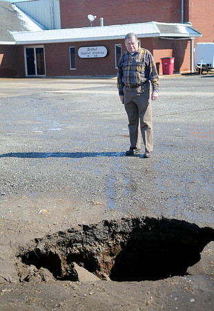 Rev. Wesley Byrd stands near one of two sinkholes at Bethel Baptist Church and Academy Wednesday, Feb. 13, 2013. (Staff Photo by BONNIE VCULEK)