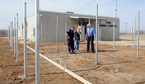 Allen Elder, supervisor of the Enid Animal Control facility, Rachel Hancock and Enid Police Chief Brian O'Rourke walk through the new outside run area Friday, Feb. 8, 2013. Construction workers will pour concrete next Wednesday. (Staff Photo by BONNIE VCULEK)