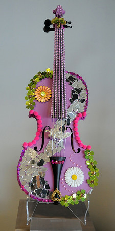 """Dan Long of Uptown Florist designed the fun and whimsical """"Hard Rock Fiddle"""" for Enid Arts Council Feastin' & Fiddlin' at Oakwood Mall, Friday, Feb. 22, 2013 from 7-11 p.m. Long, an Enid artist, has worked in the floral industry for more than thirty years. (Staff Photo by BONNIE VCULEK)"""