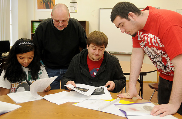 Lincoln Academy students (front, from left) Emerina Emerold, Cody Sellers and Mikel Rose work on their senior portfolios with their English 4 teacher, Kent Chesser, Tuesday, Feb. 19, 2013. In addition to teaching the English 4 classes during the day, Mr. Chesser instructs English 1-4 at night, vocational training for students and online learning. (Staff Photo by BONNIE VCULEK)