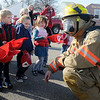 Pre-K students react as Enid firefighter, Michael Murphy, dons his firefighting gear during a special visit at Applewood Early Learning Friday, Feb. 8, 2013. Children in the Hollow class, under the direction of Barbara Fleece and Deborah Stadler, toured the Enid Fire Safety House and walked around Enid Fire Department's Engine 1 as Enid Firemen explained the tools that they use to fight fires. (Staff Photo by BONNIE VCULEK)