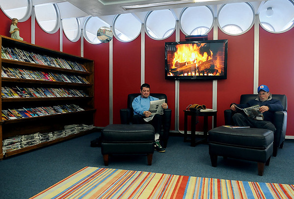 Gregory Goodman and Bobby Oakes relax near the virtual fireplace at the Public Library of Enid and Garfield County Friday, Feb. 22, 2013. (Staff Photo by BONNIE VCULEK)