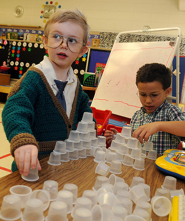 "Dominick Wacker (left) sports a crocheted cardigan and oversized, glass frames as he and Markell Jackson build a structure with 100 miniature cups during the ""Centenarian"" dress up day, celebrating the 100th day of the school year at Adams Elementary School Friday, Feb. 1, 2013. (Staff Photo by BONNIE VCULEK)"