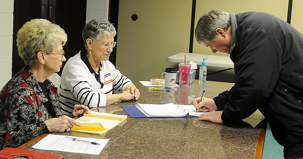 Horace Stutchman signs in before he casts a ballot for a city commission candidate at the Mennonite Bretheren Church, 2500 N. Van Buren, Tuesday, Feb. 12, 2013. Garfield County Election Board staff members (from left) Shirley Sharp and Barbara Phillips assisted during the election.(Staff Photo by BONNIE VCULEK)