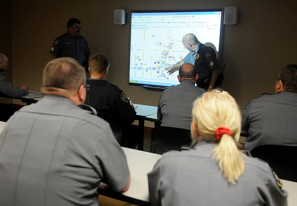 Sgt. Rick Sutton (left) and Sgt. Quent Tubbs (right) take turns discussing patrol areas during an Enid Police Department muster Thursday, Feb. 14, 2013. (Staff Photo by BONNIE VCULEK)