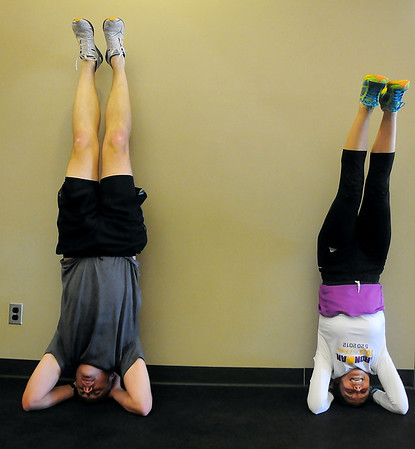 Jimmy Stallings and Lynn Mattix (from left) practice headstands during Stallings's training session at GYM Tuesday, Feb. 5, 2013. (Staff Photo by BONNIE VCULEK)
