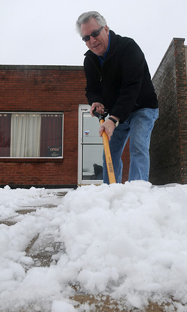 Jim Wright, a Farmers Insurance Group agent in Enid, clears snow and ice from the sidewalk in front of his business at 717 W. Broadway Thursday, Feb. 21, 2013. The winter blast brought rain, lightning, snow and sleet overnight as temperatures dropped into the upper 20s. By Thursday afternoon another round of snow moved through Garfield County. (Staff Photo by BONNIE VCULEK)