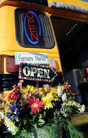 """An """"Open"""" sign flashes on and off as customers arrive at Farmers Market Tuesday, Feb. 5, 2013. Paulette Rink, the traveling desperado with Rowdy Stickhorse, opens her yellow school bus every week during the winter market days at Hope Outreach. She carries products from approximately 25 different local rural farmers. (Staff Photo by BONNIE VCULEK)"""