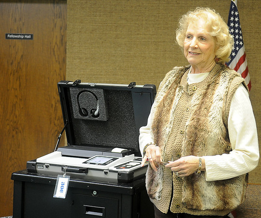 Eloise Bleakley assists voters at the Mennonite Brethren Church polling location during the Enid City Commission races Tuesday, Feb. 12, 2013. (Staff Photo by BONNIE VCULEK)