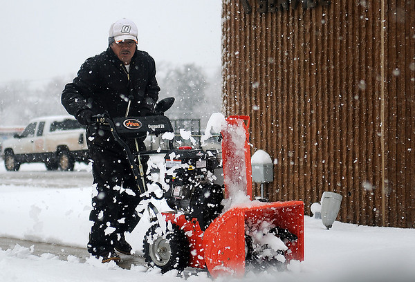 A gentleman uses an Ariens Compact 20 snow blower to clear sidewalks around the Security National Bank's location at the corner of Independence and Maine Wednesday, Feb. 20, 2013. (Staff Photo by BONNIE VCULEK)