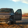 An Enid police officer gathers information from a pick-up in an accident Monday evening with another pick-up at the intersection of 42nd and E. Garriott. (Staff Photo by BILLY HEFTON)