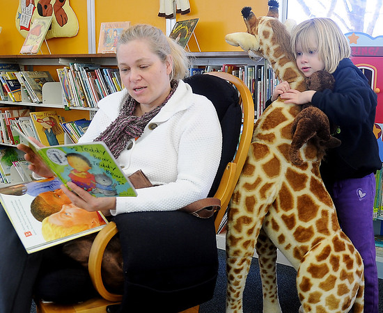 Saige Rodgers (right) snuggles up with stuffed animals as her mom, Chantell Tiatrakul, reads to her at the Public Library of Enid and Garfield County Friday. (Staff Photo by BONNIE VCULEK)