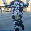 Pete Shayhorn, portrays a bovine, as he crosses the finish line during the Junior Welfare League Warm Your Heart 5K and fun run in downtown Enid, Saturday, Feb. 2, 2013. (Staff Photo by BONNIE VCULEK)