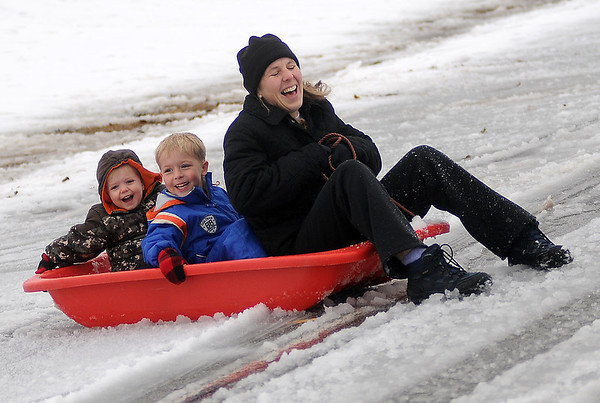 A mother and her two children laugh as they reach the bottom of the South Van Buren overpass slope Thursday, Feb. 21, 2013. With area school closings due to the winter storm, families enjoyed the afternoon sledding. (Staff Photo by BONNIE VCULEK)