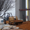 A heavy equipment operator moves and levels dirt around the new Enid High School University Center Wednesday, Feb. 6, 2013. The center is slated to open in August. (Staff Photo by BONNIE VCULEK)