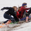 Enid High School soccer players (from left) Kaitlin Bell, Kamika Ralstin, Claudia Huerta and Sarah Blakley sled into cold muddy water on the South Van Buren overpass slope Thursday, Feb. 21, 2013. As temperatures dropped into the upper 20s, the winter blast brought lightning, heavy rain, snow and sleet, canceling classes for schools and colleges across Enid and most of Oklahoma. (Staff Photo by BONNIE VCULEK)