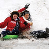 Kamika Ralstin,left, Sarah Blakley, back, and Claudia Huerta sled down the slope of the South Van Buren overpass Thursday, Feb. 21, 2013, in Enid, Okla. Temperatures dropped into the upper 20s, as an upper level winter storm produced lightning, heavy rain, freezing rain, snow and thunder sleet, closing schools and colleges across Enid and most of Oklahoma. (AP Photo/Enid News and Eagle, Bonnie Vculek)