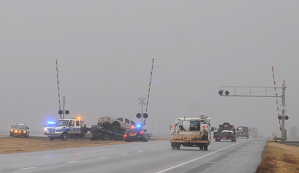 Oklahoma Highway Patrol, Troop J, and Garfield County Sheriff Department deputies investigate a train-truck crash as Stanley's Wrecker Service prepares the truck for transport Thursday, Feb. 7, 2013. (Staff Photo by BONNIE VCULEK)