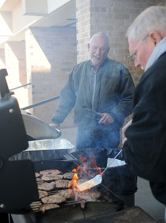 Tommy Williams and Paul Davis (from left) grill hamburgers and hot dogs for the residents at Meadows Point Apartments Wednesday, Feb. 27, 2013. Electricity to the 5-story facility has been off since late Monday evening when the winter storm moved across Garfield County. (Staff Photo by BONNIE VCULEK)