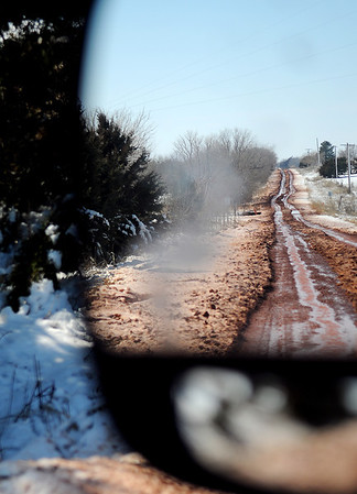 A muddy trail on a rural Garfield County road reflects in a driver's side mirror Wednesday, Feb. 27, 2013. Enid and rural residents are still without electrical power following Monday's major winter storm. OG&E crews have been working around the clock to restore service to more than 19,000 customers. (Staff Photo by BONNIE VCULEK)
