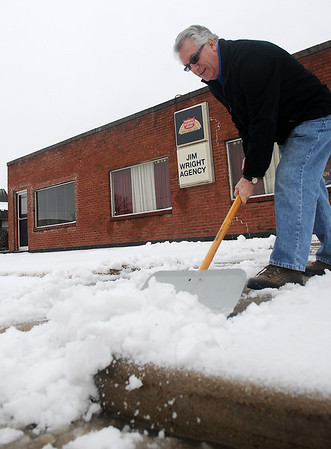 Jim Wright clears snow and ice from the sidewalks in front of his Farmers Insurance Group Agency Thursday, Feb. 21, 2013. Area residents saw weather conditions change from lightning and rain to snow and sleet overnight as a winter storm continued it track across northwest Oklahoma. (Staff Photo by BONNIE VCULEK)