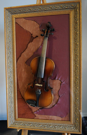 This art piece is a vintage violine with a vintage frame. The new leather background accentuates the piece. The markings on the inside of the item are: Antonius Stradivarius Cremonenfis Faceibat Anno 17. Stradivari is believed to have made around 1,100 instruments in his lifetime; roughly 500 violins remain. No matter the violin's value, the beautiful piece of art will be the silent auction item donated by The Northcutt Family at the Enid Arts Council Feastin' and Fiddlin' at Oakwood Mall Friday, Feb. 22, 2013. (Staff Photo by BONNIE VCULEK)