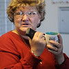 Linda Brooks clutches a hot cup of coffee as she and residents wait for the electricity to come back on at Meadows Point Apartments Wednesday, Feb. 27, 2013. (Staff Photo by BONNIE VCULEK)