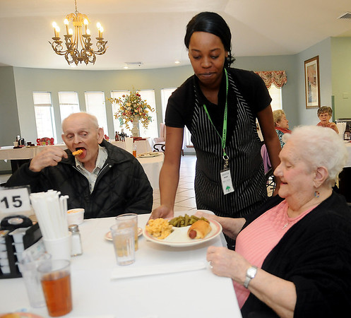 Shontae Outley, Greenbrier dietary staff member, serves Melba Best a meal Wednesday, Feb. 13, 2013. Clients at Greenbrier may select a special meal each day or order from the regular menu. The staff follows the client's dietary needs. (Staff Photo by BONNIE VCULEK)