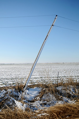 Several high line poles, like the one shown, are snapped off at the base along Skeleton Road Wednesday, Feb. 27, 2013. OG&E crews have worked around the clock since Monday's winter storm caused thousands of power outages across Enid and surrounding rural communities. (Staff Photo by BONNIE VCULEK)