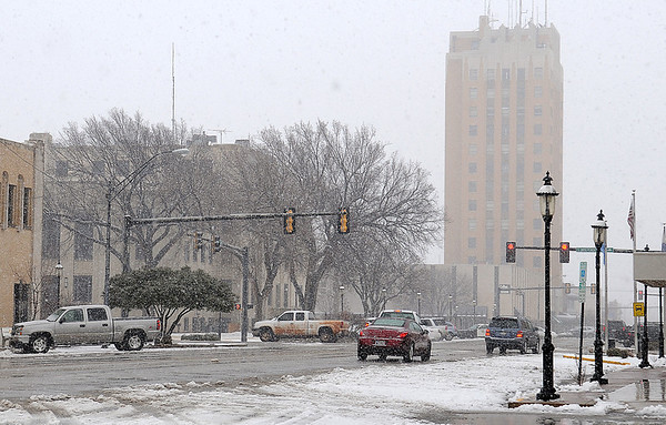 Traffic moves along W. Broadway as snow begins to fall again Thursday, Feb. 21, 2013. According to the National Weather Service, overnight temperatures will drop into the teens. (Staff Photo by BONNIE VCULEK)
