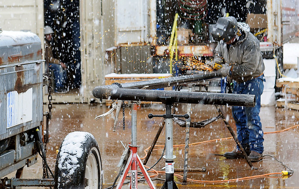 As snow falls, a worker grinds a metal fitting during construction on the new Enid High School University Center Tuesday, Feb. 12, 2013. (Staff Photo by BONNIE VCULEK)