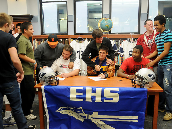 Enid HIgh School Plainsmen (seated, from left) Logan Miller, Seth Handley and Lance Smith, receive congratulations from their teammates during their letter of intent signing in the EHS Library Wednesday, Feb. 6, 2013. (Staff Photo by BONNIE VCULEK)