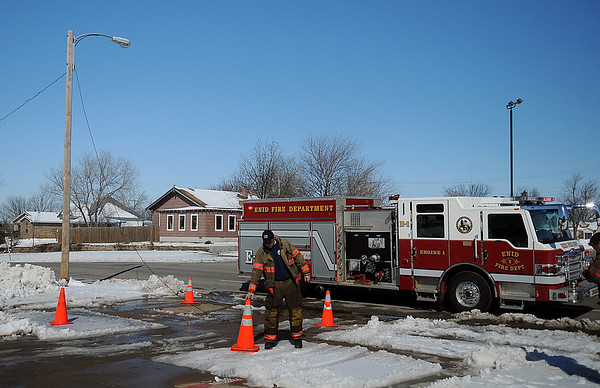An Enid firefighter places warning cones around a downed electric line at the entrance to Loaves & Fishes as Enid firefighters wait for OG&E to respond to the location Wednesday, Feb. 27, 2013. (Staff Photo by BONNIE VCULEK)
