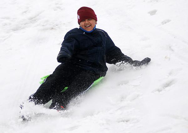 Josue' Huerta flies down the South Van Buren overpass slope as he sleds during the wintery school closings Thursday, Feb. 21, 2013. (Staff Photo by BONNIE VCULEK)