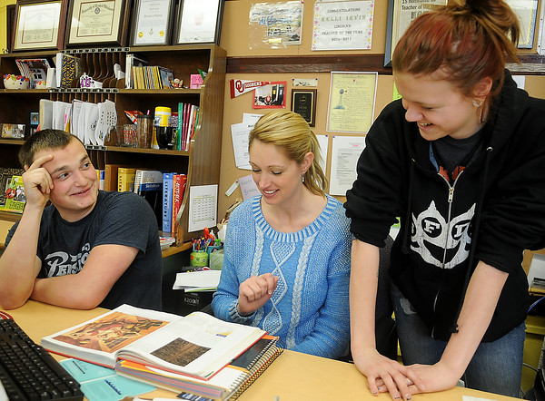 Mrs. Kelli Irvin (center), English 3 and Art instructor for Lincoln Academy, discusses a writing assignment with Tyler McNeill (left) and Ciara Zumalt Tuesday, Feb. 19, 2013. (Staff Photo by BONNIE VCULEK)