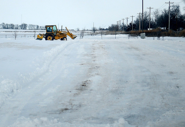A heavy equipment operator keeps Prairieview Elementary School driveways clear of snow since parents had difficulty dropping their children off for classes early Wednesday, Feb. 5, 2014. (Staff Photo by BONNIE VCULEK)