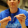 Tami Ross, from McConaghie Dental Lab in Oklahoma City, examines two new flippers, or partials, specifically created for dental patients during the 5th annual Oklahoma Mission of Mercy at the Chisholm Trail Expo Center Saturday, Feb. 8, 2014. More than 2,000 dental professionals and volunteers assisted 2,000 patients during the two-day event presented by the Oklahoma Dental Association, Oklahoma Dental Foundation, Oklahoma Delta Dental Oral Health Foundation and endorsed by the Oklahoma State Department of Health. (Staff Photo by BONNIE VCULEK)