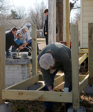 Robert Perry and Monty Gearhart assist Ron Lewis down the front steps at 831 E. Pine as the Enid Noon AMBUCS build a handicap ramp for Lewis Saturday, Feb. 22, 2014. (Staff Photo by BONNIE VCULEK)