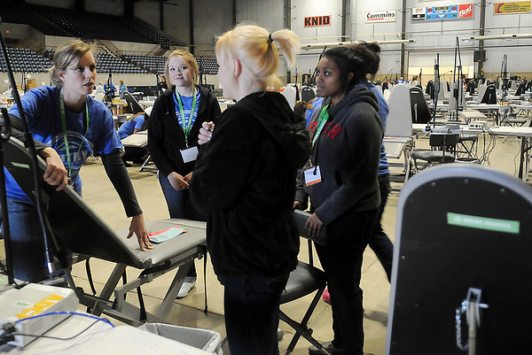 Autry Technology Center dental and medical assistant students and instructors help with the Oklahoma Mission of Mercy equipment set up at the Chisholm Trail Expo Center Thursday, Feb. 6, 2014. Due to the frigid temperatures, clients will be able to enter the Pavilion beginning at 5 p.m. this afternoon instead of waiting in line outside the Expo Center. Following an opening ceremony, free dental care will begin on more than 100 patients at a time during the two-day event. More than 2000 volunteers will assist. (Staff Photo by BONNIE VCULEK)