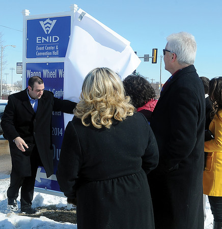 "Dignitaries watch as Keller Taylor, general manager of the Enid Event Center and Convention Hall, unveils a new street sign Tuesday, Feb. 11, 2014, officially renaming Independence Avenue Wagon Wheel Way"" in honor of the sold-out Darius Rucker concert on March 7, 2014. Global Spectrum, operators of the Enid Event Center, and the City of Enid renamed Independence Avenue, between Owen K. Garriott and Maine Street, for the month leading up to the concert. (Staff Photo by BONNIE VCULEK)"