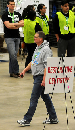 Dr. Tim Fagan, president of the Oklahoma Dental Association and chair of Mission of Mercy, walks past a restorative dentistry sign as volunteers, dental assistants and more than 300 dentists provide free dental care during the 5th annual Oklahoma Mission of Mercy at the Chisholm Trail Expo Center Friday, Feb. 7, 2014. (Staff Photo by BONNIE VCULEK)