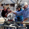 Monty Gearhart, with the Enid Noon AMBUCS, cuts a treated board during the handicap ramp build at 831 E. Pine Saturday, Feb. 22, 2014. (Staff Photo by BONNIE VCULEK)