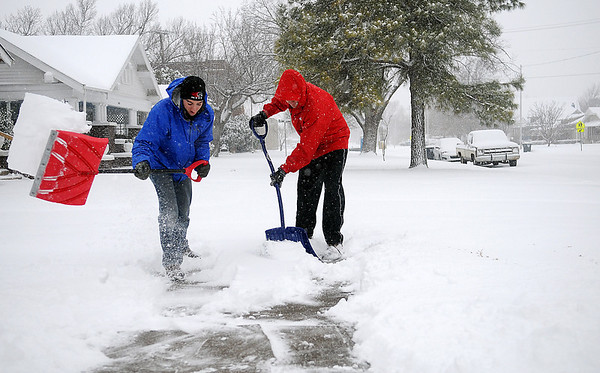 Nate Mocalis (left) and Joe Roche shovel their sidewalk and driveway at 1619 W. Broadway as heavy snow continues to fall Tuesday, Feb. 4, 2014. Schools in Enid, Garfield County and much of the Oklahoma closed because of the inclement weather. (Staff Photo by BONNIE VCULEK)