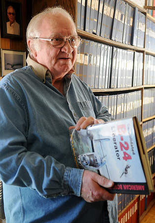"John Campbell shares a memory of his childhood as he holds his published book ""Consolidated B-24 Liberator Saturday, Feb. 22, 2014. Campbell owns one of the largest private collections of aircraft photographs. (Staff Photo by BONNIE VCULEK)"