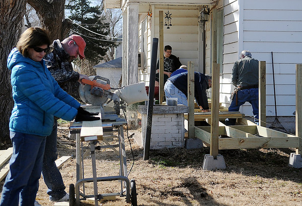 Jonathan Lewis (top center) watches the Enid Noon AMBUCS build a handicap ramp for his father, Ron Lewis, at 831 E. Pine during AMBUCS National Service Day Saturday, Feb. 22, 2014. (Staff Photo by BONNIE VCULEK)