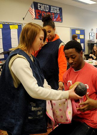 "Mackenzie Miles (left) and Keara Jenkins wear ""The Empathy Belly"" as Miles hands Marshawn Mills one of the eight computer programmed babies that the students must care for as part of their ""Baby Think It Over"" weekend project in Kathy Gilliland's Family and Consumer Science classes at Enid High School Thursday, Feb. 20, 2014. (Staff Photo by BONNIE VCULEK)"
