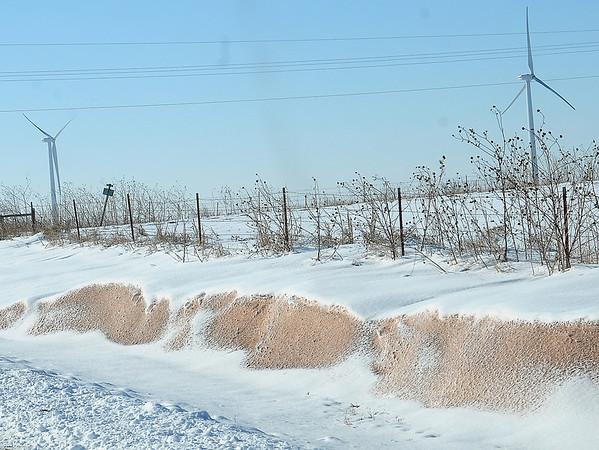 Wind turbines appear in the distance as snowdrifts line a fence near Kremlin Tuesday, Feb. 11, 2014. (Staff Photo by BONNIE VCULEK)