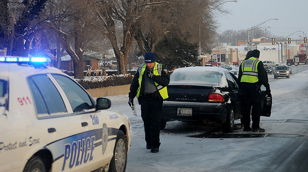 Enid Police officer work an accident near the intersection of S. Van Buren and W. Wabash Thursday, Feb. 6, 2014. Single digit temperatures overnight and new snowfall made driving slick and hazardous during the morning drive to work for area residents. (Staff Photo by BONNIE VCULEK)