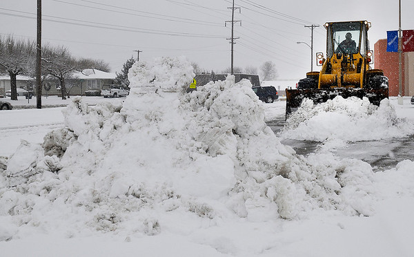 A front end loader clears the parking lot at Sunset Plaza Tuesday. (Staff Photo by BILLY HEFTON)