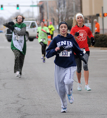 Tyler Berge sprints ahead of a group of runners during the Junior Welfare League Warm Your Heart 5K in downtown Enid Saturday, Feb. 01, 2014. Berge finished the race in 25:26 winning the female 13-19 age group. (Staff Photo by BONNIE VCULEK)